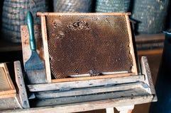 Мастерская ` s Beekeeper, полная сота меда с шабером рядом с ним готовым для того чтобы подготовить стоковая фотография rf
