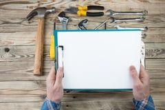 Мастерские руки ремонта держа бумагу стоковые изображения