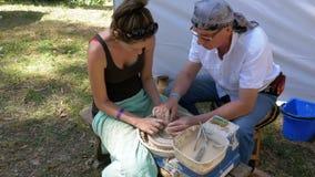 Мастерский класс в гончарне ` S гончара женщины и старика работает с глиной на колесе ` s гончара видеоматериал