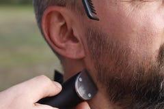 Мастерский парикмахер режет человека бороды Стоковые Фотографии RF