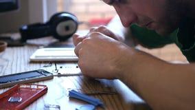 Мастерский ремонтируя сломанный телефон, тщательно собирает точные детали выкупа на таблице 3840x2160 4K акции видеоматериалы