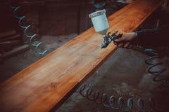 Мастерский художник в фабрике - промышленная древесина картины с оружием брызга Стоковое Фото