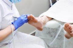 Мастерский chiropody формирует ногти Мужской пациент в процессе процедуры по pedicure оборудования Внимательность тела принципиал Стоковое Изображение RF