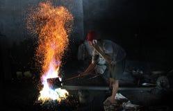 Мастеры традиционных gamelan аппаратур обрабатывают один гонг gamelan ремесла аппаратур а именно gamelan в центре в Стоковое фото RF