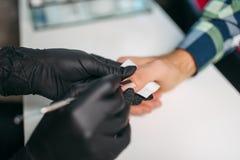 Мастер в перчатках полируя ногти к мужскому клиенту стоковая фотография rf