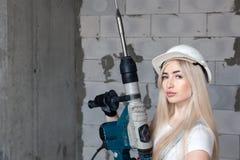 Мастер девушки крупного плана белокурый в белом шлеме конструкции держа профессиональный перфоратор, сверлит в доме под конструкц стоковые фото
