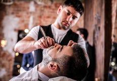 Мастер делает коррекцию бород в салоне парикмахерскаи Закройте вверх по фото Стоковые Изображения