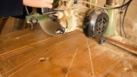 Мастер использует круглую пилу для того чтобы сделать отрезок к части грубой древесины в его домашней мастерской видеоматериал