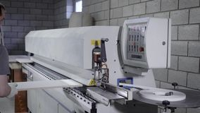 Мастер использует промышленную машину для обрабатывать края доски частицы в мастерской завода мебели сток-видео