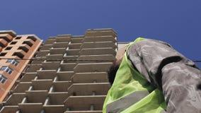Мастер конструкции с бородой и усиком нося шлем на фоне дома под конструкцией 4K видеоматериал