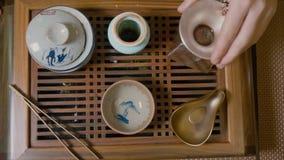 Мастер льет горячую воду в шаре с верхней частью зеленого чая вниз с взгляда Церемония чая акции видеоматериалы