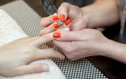 Мастер пил маникюра и присоединения ноготь формирует во время процедуры расширений ногтя с гелем в салоне красоты стоковые изображения rf