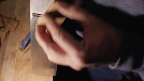 Мастер плотника строгает деревянный гребень, обрабатывая свои края с плоским концом вверх 4 k видеоматериал