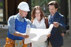 Мастер показывает планы дома к парам Стоковое Фото