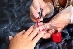 Мастер покрывает красные ногти геля Стоковая Фотография