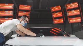 Мастер полирует автомобиль в мастерской автомобиля акции видеоматериалы