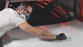 Мастер полирует автомобиль в мастерской автомобиля сток-видео