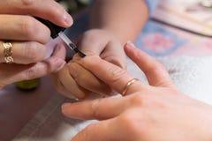 Мастер прикладывает блеск на ногтях процесс создания конца-вверх рук маникюра позаботьте ноготь ногтя хлопка извлекая политуру пр стоковое изображение rf