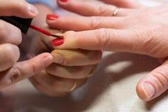 Мастер прикладывает блеск на ногтях процесс создания конца-вверх рук маникюра позаботьте ноготь ногтя хлопка извлекая политуру пр стоковая фотография rf