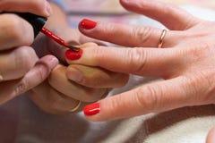 Мастер прикладывает блеск на ногтях процесс создания конца-вверх рук маникюра позаботьте ноготь ногтя хлопка извлекая политуру пр стоковое фото