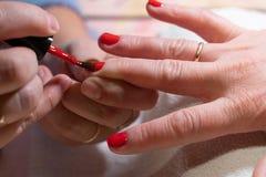 Мастер прикладывает блеск на ногтях процесс создания конца-вверх рук маникюра позаботьте ноготь ногтя хлопка извлекая политуру пр стоковые фото