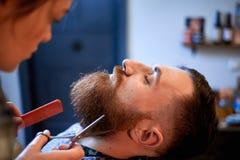 Мастер режет волосы и бороду людей в парикмахерскае Стоковое Изображение RF