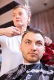 Мастер режет волосы человека в салоне Ножницы, конец-вверх Roschetsk Парикмахерские услуги концепции, стрижка, красота стоковое фото