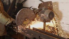 Мастер режет длинную деталь металла мощной промышленной круглой пилой акции видеоматериалы