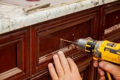 мастер сверлит дверь в двери шкафа Стоковая Фотография