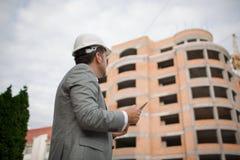 Мастер смотря новое современное здание на промышленной предпосылке Концепция технологий строительства скопируйте космос Стоковое фото RF