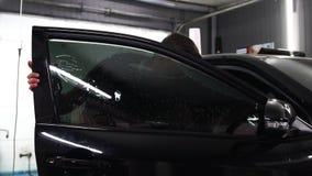 Мастер устанавливает фильм подкраской для стекла автомобиля с феном для волос и шпателем с слепимостью света Подкрашивать концепц