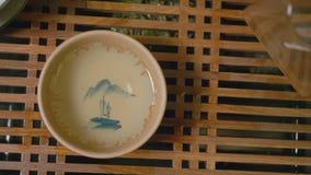 Мастер чая лить горячий чай от стеклянного кувшина во взгляд шара чая надземный видеоматериал