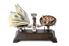 Масштабы, деньги и золото изолированные на белой предпосылке Стоковое Изображение