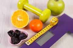 Масштаб цифров, сантиметр, гантели и плодоовощи, здоровое питание и концепция уменьшения Стоковая Фотография