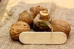 Масло грецкого ореха на винтажной бутылке и гайках на грубом увольнении ткани Стоковая Фотография RF