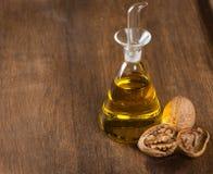 Масло и гайки грецкого ореха на деревянном столе Стоковое Изображение RF