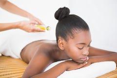 Масло массажа Masseuse лить на милой задней части женщины стоковая фотография