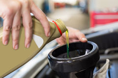 Масло механика лить в автомобиль стоковое изображение
