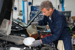 Масло механика лить в двигателе автомобиля Стоковое Фото