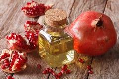 Масло семени гранатового дерева в стеклянной бутылке на таблице горизонтально стоковое изображение rf