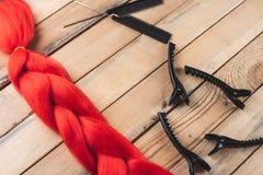 Материал Kanekalon красный на деревянной предпосылке около зажимов и гребней стоковое фото rf