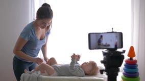 Материнская забота, известная мама блоггера изменяет одежды младенческого мальчика пока записывающ видео- урок на сотовом телефон сток-видео