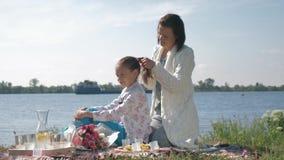 Материнская забота, счастливая мама делает оплетку дочери во время остатков на пикнике семьи около озера акции видеоматериалы