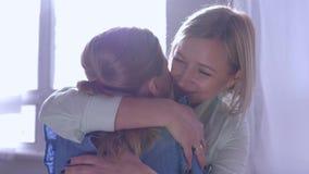 Материнская любовь, маленькая девочка спешит в руки мамы и дает большое объятие и целует дома против окна в лучах солнца
