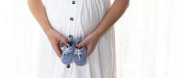 материнствй Руки женщины держа поднимающее вверх ботинок младенца близкое Принципиальная схема всеединства, поддержки, предохране Стоковое Изображение
