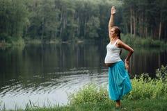 Материнство беременной йоги пренатальное делая различные тренировки в парке на траве, дышать, протягивая, статика стоковые изображения