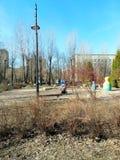 Матери и дети на спортивной площадке в парке стоковые изображения