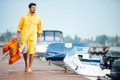 Матрос в желтом плаще на пристани держа спасательный жилет Стоковое Изображение