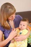 Мать дает к больной медицине младенца посредством batcher стоковые изображения rf