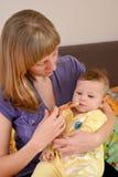 Мать дает к больной медицине младенца посредством batcher стоковое фото rf